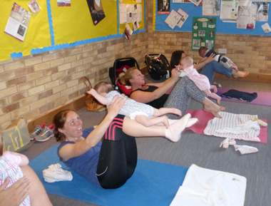 mums and babies practicing yoga exercises